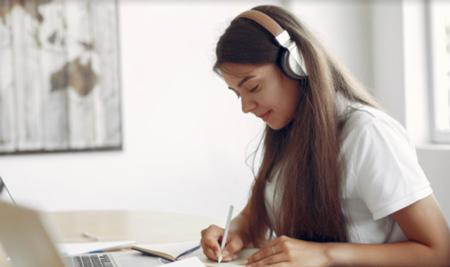 Young woman studying with headphones